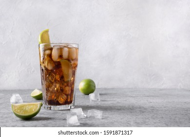 Cocktail Cuba Libre or long island iced tea with rom, cola, lime and ice in glass on grey stone table. Horisontal orientation.