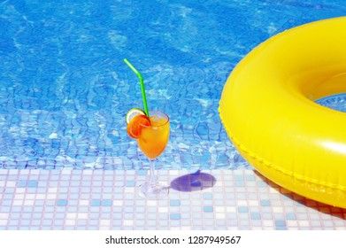Cocktail drink close to swimming pool, summer vacation concept