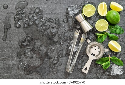 Cocktail drink making tools and ingredients with ice on dark stone background. Flat lay