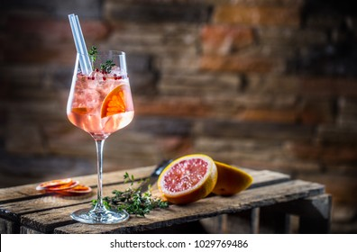 Cocktail drink on a old  wooden board. Alcoholic beverage with tropical fruits red pepper herb and ice.