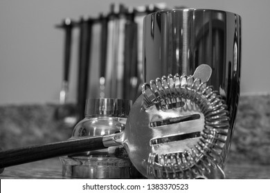 Cocktail drink shaker mix stainless steel device and strainer arranged on bar counter top in black and white decor art photo for decoration