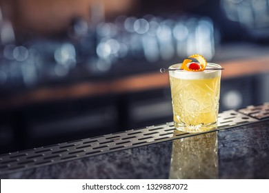 Cocktail drink whiskey sour at barcounter in night club or restaurant.