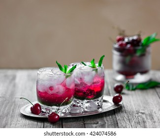 A cocktail with gin, mint liqueur, cherry syrup and pieces of ice on vintage background