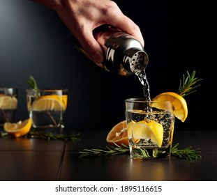 Cocktail Gin and Tonic with lemon and rosemary. The bartender pours a cocktail from a shaker into a glass. - Shutterstock ID 1895116615