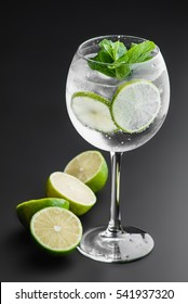 "cocktail ""gin and tonic"" on a dark uniform background with lime"