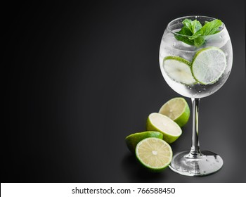 "cocktail ""gin and tonic"" on a dark uniform background with lime."