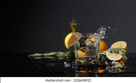 Cocktail gin-tonic with lemon slices. Piece of ice falls into the glass. Copy space.