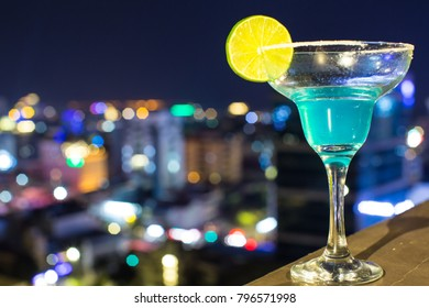 Cocktail glass of blue margarita lemon decoration on gold stone table blurred bokeh background of cityscape.