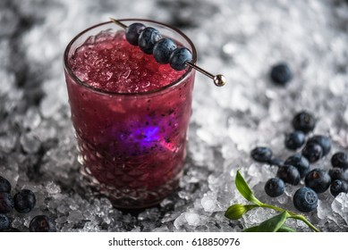Cocktail in a glass, blueberry and orchid flower on ice against a dark background. A close-up of a drink of fresh lemonade.