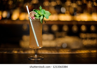 Cocktail glass filled with tasty Sherry Cobbler drink decorated with mint, straw and orange slice on bar counter
