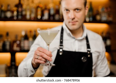 Cocktail glass with fresh alcoholic drink in bartenders hand
