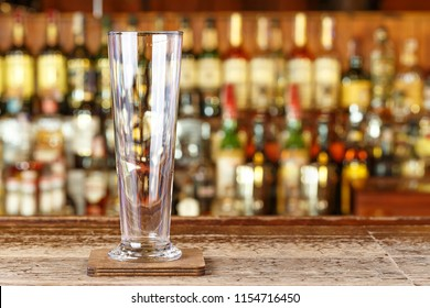 A cocktail glass on the blurred background of the bar, the start of a night club party