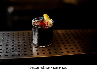 Cocktail glass with strong dark bittersweet cocktail decorated with slices of fresh lemon on bar