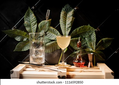 Cocktail glass with yellow summer cocktail, bottle with red liquor and bar utensils arranged on the background of green leaves and black wall on wooden box