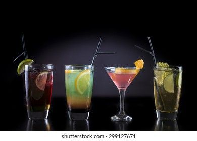 Cocktail glasses isolated on black / Cocktail bar glasses with cocktails on black background / Cocktail drinks in various glasses isolated
