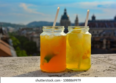 Cocktail glasses with refreshing lemonade on table in rooftop bar against city view. Beautiful rooftop bar in Budapest, Hungary.