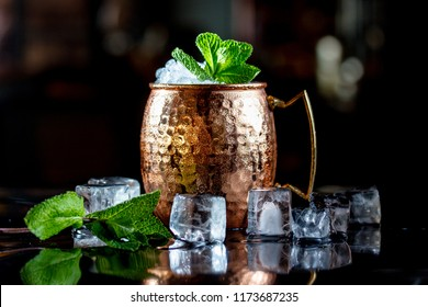 Cocktail with ice, in a copper mug on a black background.