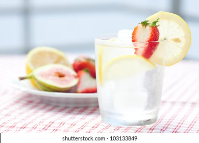 cocktail with ice,lemon, fig and strawberries on a plate