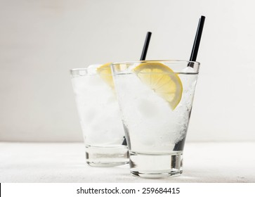 Cocktail with lemon and ice in a glass on the white wooden table