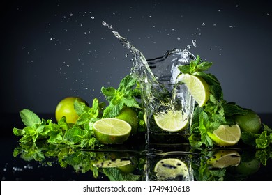 Cocktail with limes and mint on a black reflective background. Lime slice fall in glass with drink.