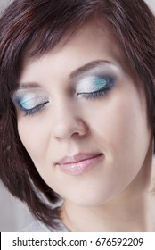 Cocktail makeup on the girl with the brown hair basic bob and clear skin. Isolated grey background.