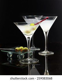 Cocktail in martini glasses with olives on black background