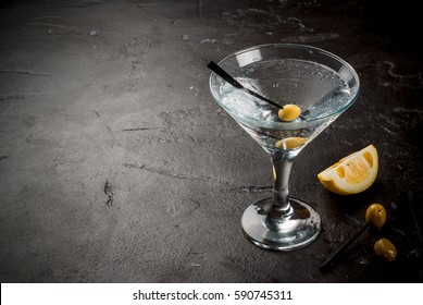 Cocktail martini with olives and a lemon on a black concrete stone table, copy space