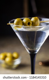 Cocktail martini with olives on gray stone background.