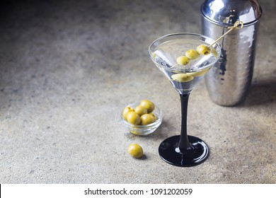 Cocktail martini with olives on stone background, copy space
