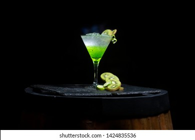 Cocktail or mocktail with kiwi and mint in a glass on a background.