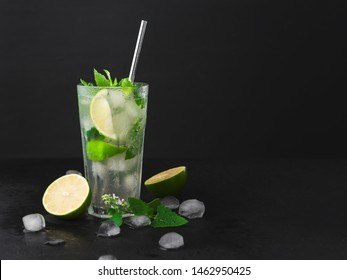Cocktail Mojito with ice in a glass, lime, leaf mint ,shaker ice cubes and metal straw on a dark background