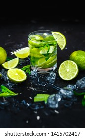 Cocktail mojito with mint, cold drink or beverage with ice and water drops on black background. Selective focus