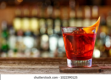 Cocktail Negroni in a nightclub on a shabby wooden bar counter.  Decorated with orange at bar background.