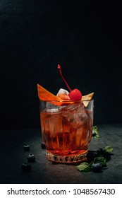 Cocktail Negroni on a black background with a cocktail cherry skin of an orange ice with mint leaves and blueberries