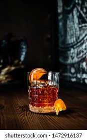 Cocktail Negroni on a old wooden board. Drink with gin, campari martini rosso and orange. negroni cocktail at the bar