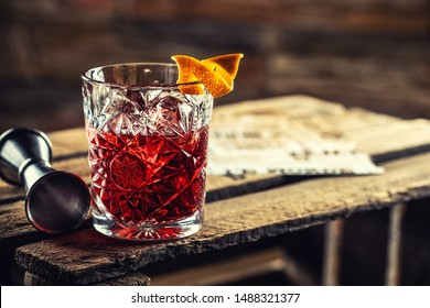 Cocktail Negroni on a old  wooden board. Drink with gin, campari martini rosso and orange.