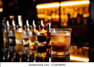 A cocktail in an old fashioned glass on a bar counter with a reflection, bottles with bitters, bokeh lights, horizontal photo