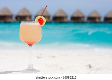 Cocktail on a beach with red cherry