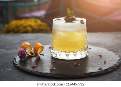 Cocktail on rustic wood background. Cold citrus alcohol beverage with tequila, blood juice and ginger beer, served with citrons and ice, copy space