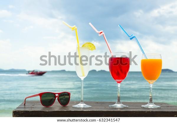 cocktail orange juice,wine,lemon and red glasses on sea background