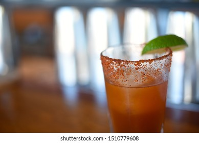 Cocktail with peppered rim and lime wedge on a bar.