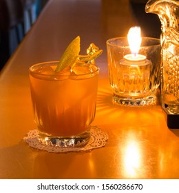 A cocktail photographed on a bartop next to candle with a warm atmosphere