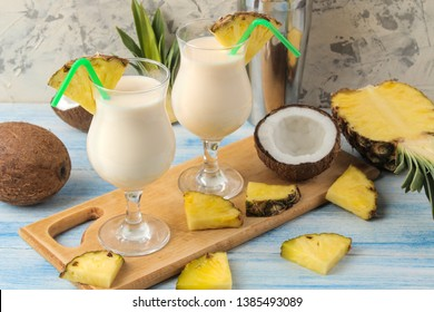 Cocktail Pina Colada. Pina Colada refreshing summer alcoholic cocktail with coconut milk and pineapple juice nearby. summer drink. cocktail preparation. on a light background and on a blue table.