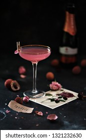 Cocktail with pink Prosecco, lychee juice, rose water on a dark background. Postcard with rose, lychee fruit. Selective focus