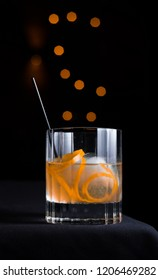 A cocktail in a rocks glass with ice sphere & orange garnish on black background with orange circles