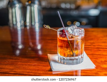 A cocktail in a rocks glass sitting on a wooden bar