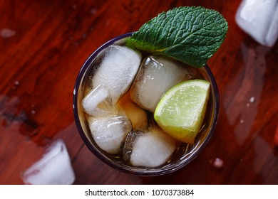 Cocktail rum and cola and ice closeup on wooden table with copy space