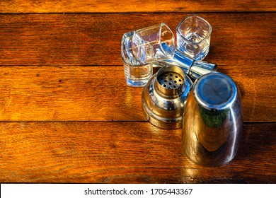Cocktail shaker accessories and shots glasses on a wooden board. Bar utensils, drinks concept