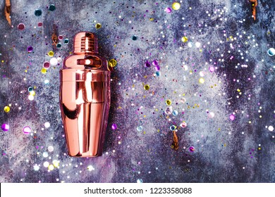 Cocktail shaker with glitter confetti on space blue background. Copy space