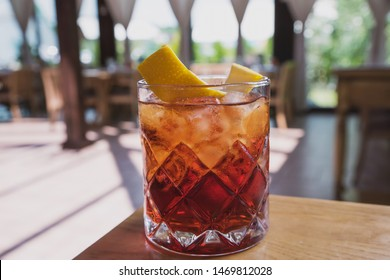 cocktail with soda, whiskey and orange zest on the background of a summer cafe on a wooden table